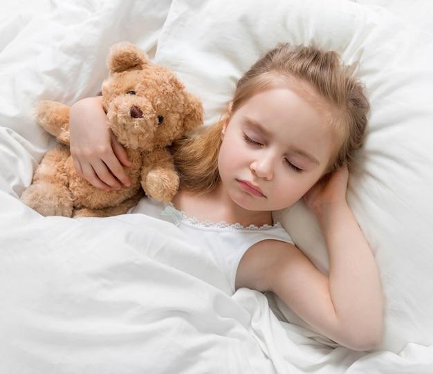 Criança dormindo com um fofo urso de pelúcia