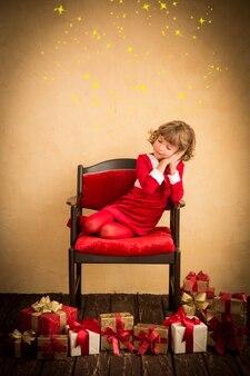 Criança dormindo na poltrona. presente de natal. conceito de férias de natal