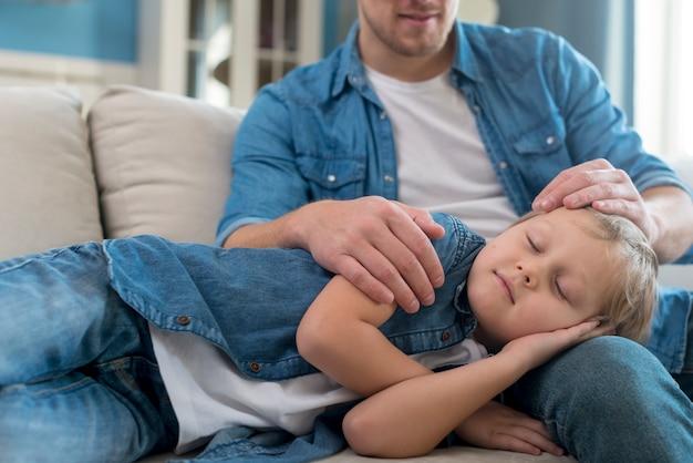 Criança dormindo nas pernas do pai