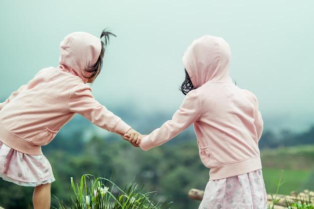 Criança, duas lindas garotas segurando a mão no jardim