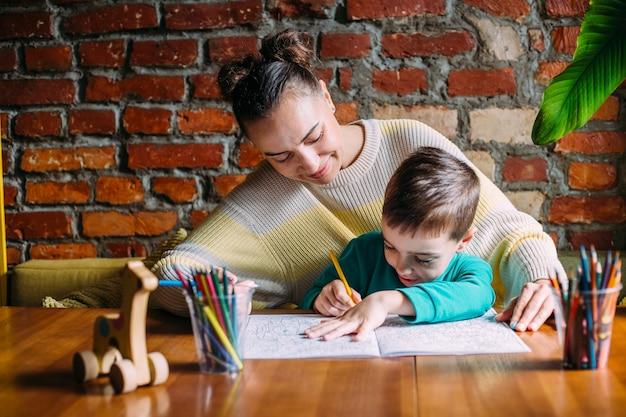 Criança e adulto desenhando um livro para colorir