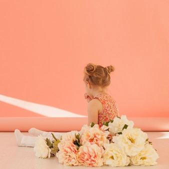 Criança e buquê de flores vista traseira