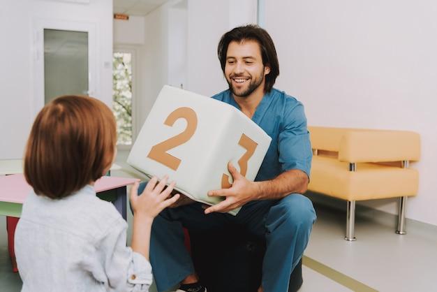 Criança e enfermeira masculina jogando na clínica pediátrica