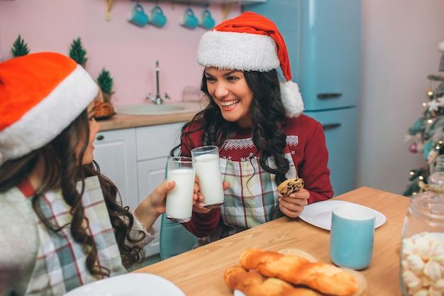 Criança e jovem simpática e positiva nos olham e sorriem. eles comemoram com copos de leite. menina sente-se à mesa na cozinha.