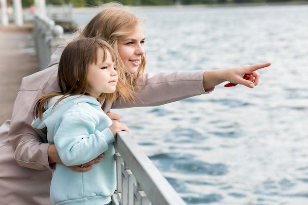 Criança e mãe à beira-mar