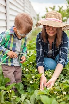 Criança e mãe cuidando de um jardim de morango no quintal