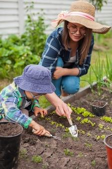 Criança e mãe cuidando de uma horta no quintal