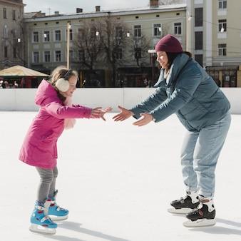 Criança e mãe patinando no exterior
