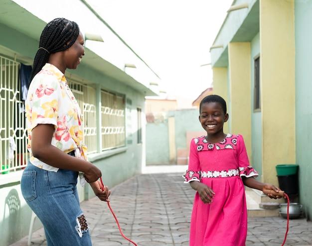 Criança e mulher de tiro médio com corda de pular