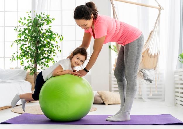 Criança e mulher treinando com bola de ginástica
