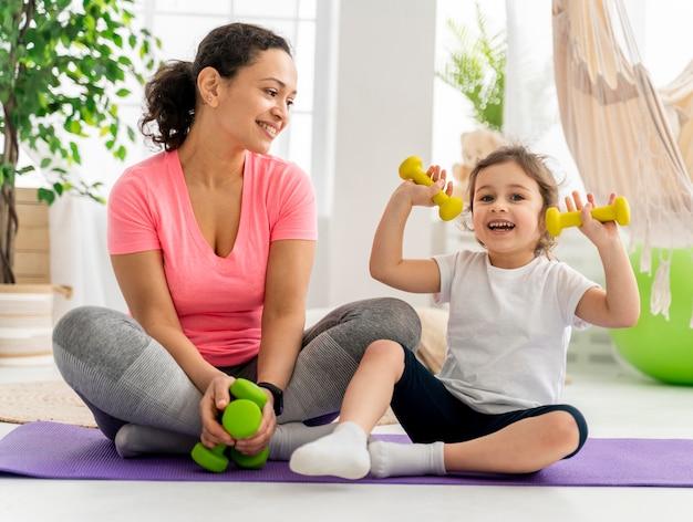 Criança e mulher treinando com halteres