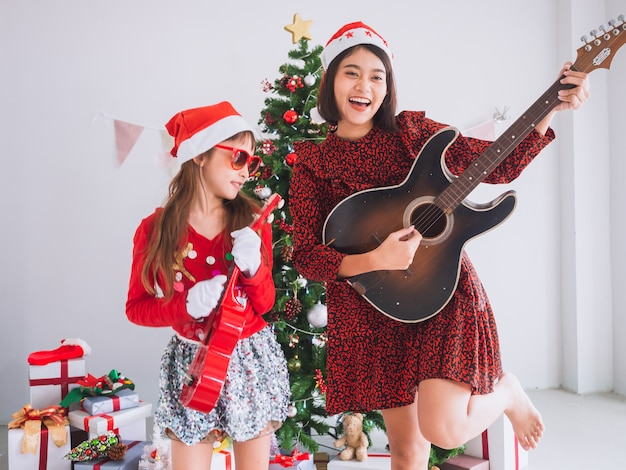 Criança e mulheres asiáticas comemoram o natal dedilhando o violão em casa