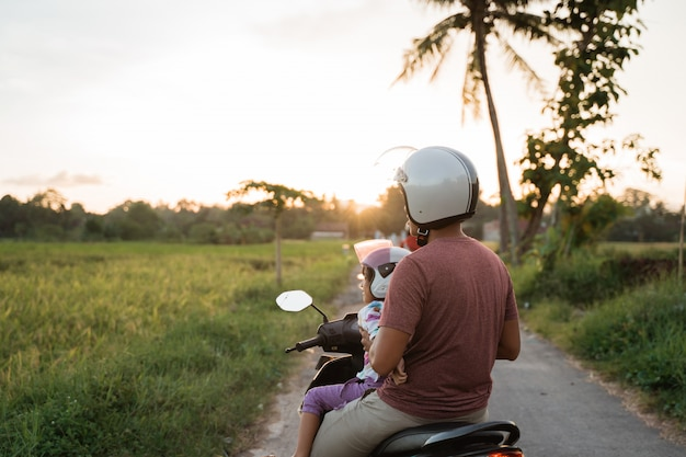 Criança e pai asiático andam de scooter de moto