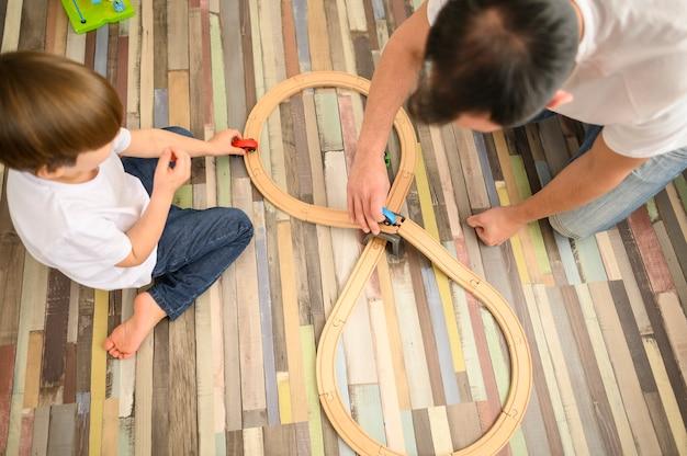 Criança e pai brincando com brinquedos