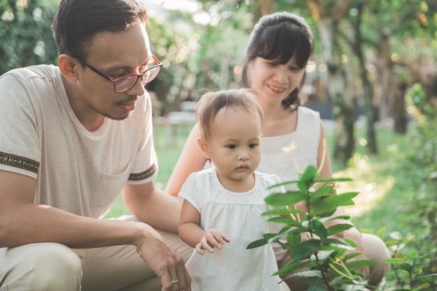Criança e pais se divertindo no jardim