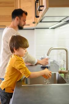 Criança e seu pai lavando limões