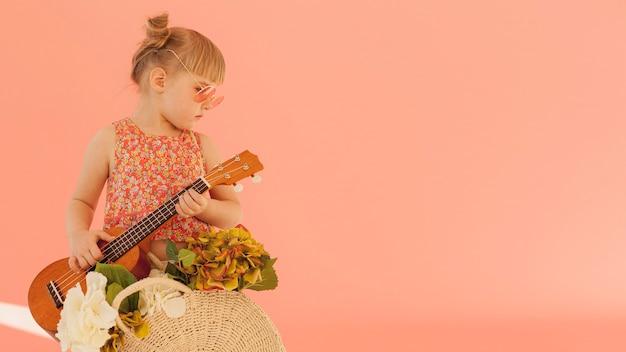 Criança elegante, segurando o violão