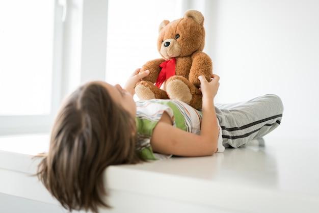 Criança em casa com ursinho de pelúcia