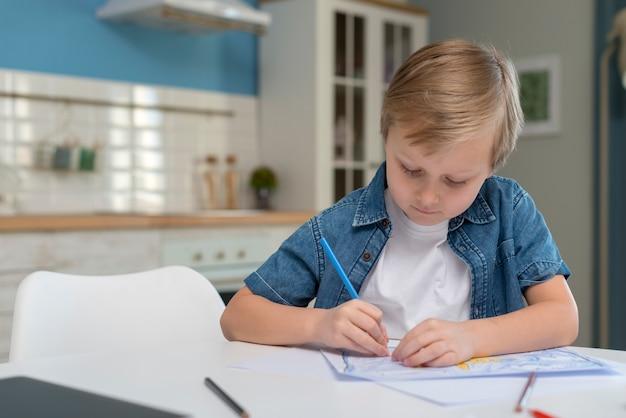 Criança em casa escrevendo e focando