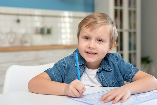 Criança em casa, escrevendo em um papel