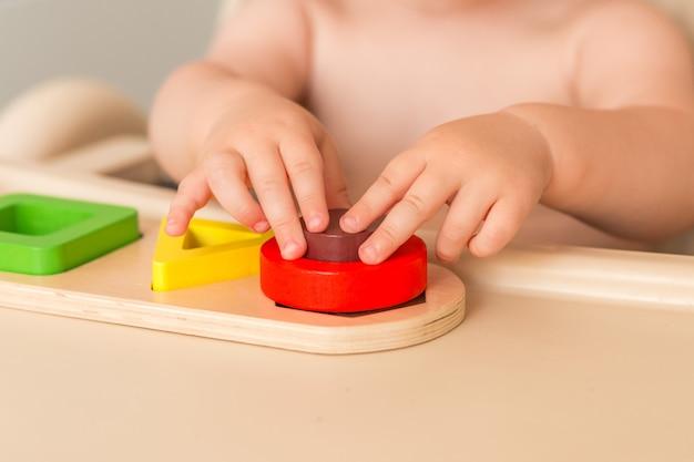 Criança em casa está manipulando material montessori para aprender