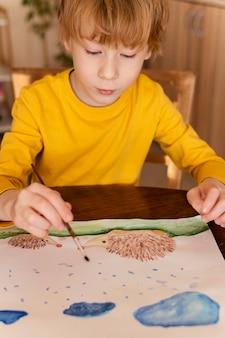 Criança em close pintando gotas de chuva