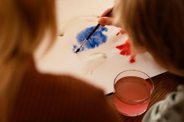 Criança em close-up pintando em papel de alto ângulo