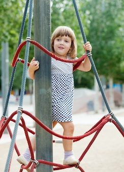 Criança em cordas no campo de jogos