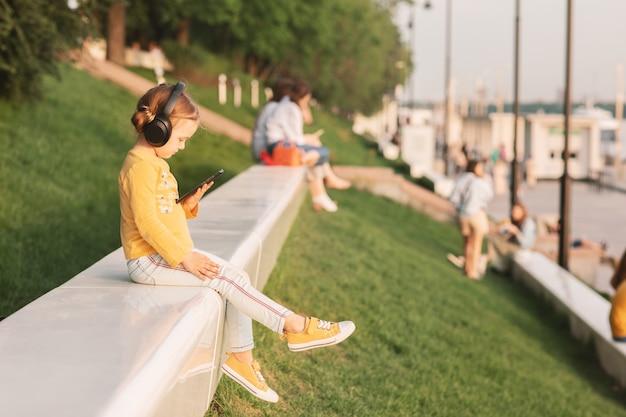 Criança em idade escolar com mochila na natureza ouve música com telefone celular e fones de ouvido. comunicação de tecnologia online. educação online na escola primária.