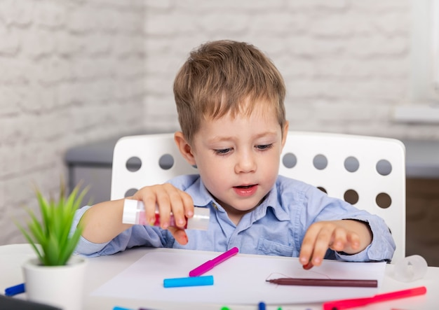 Criança em idade escolar cortando papel colorido com uma tesoura, ficando criativa