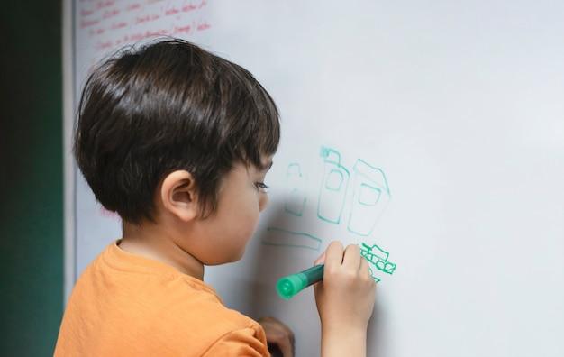 Criança em idade escolar desenhando um tanque de desenho animado no quadro branco, criança segurando uma caneta de cor, escrever a bordo, educação em casa, conceito de educação