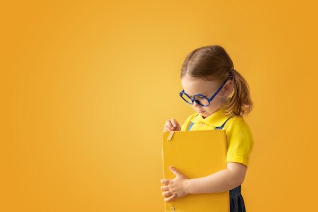 Criança em idade escolar em óculos de fundo amarelo isolado segurar livro escolar voltar para a escola educação