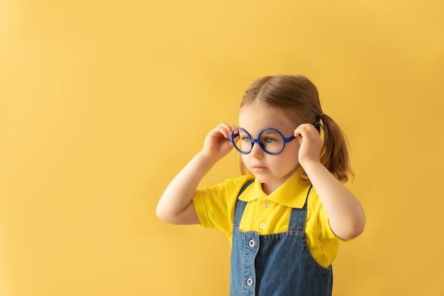 Criança em idade escolar grave em óculos de fundo amarelo isolado olhando para o espaço da cópia teste de visão de criança no olho medição de visão para crianças em idade escolar