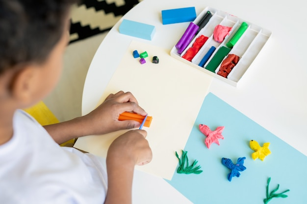 Criança em idade pré-escolar mestiça cortando plasticina laranja na mesa enquanto faz fotos de peixes engraçados em papel azul no jardim de infância