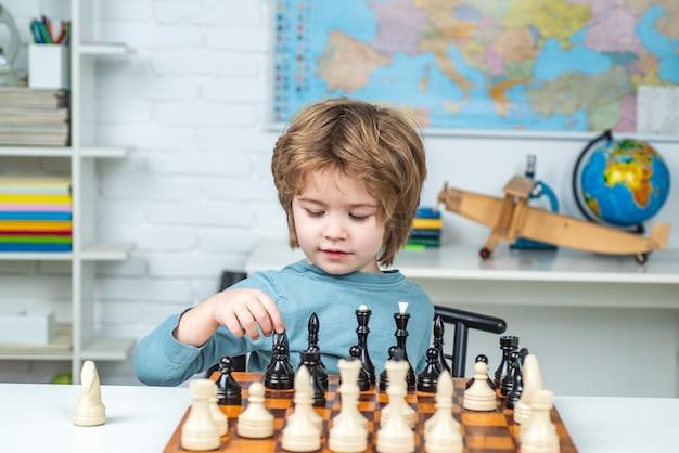 Criança em idade pré-escolar ou estudante pensando em estratégia de xadrez infantil garoto jogando xadrez