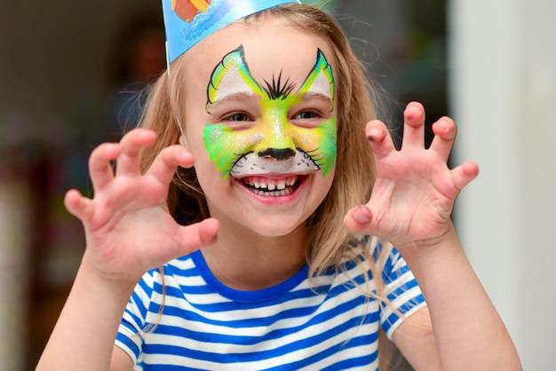 Criança em maquiagem rosna com mãos de garras