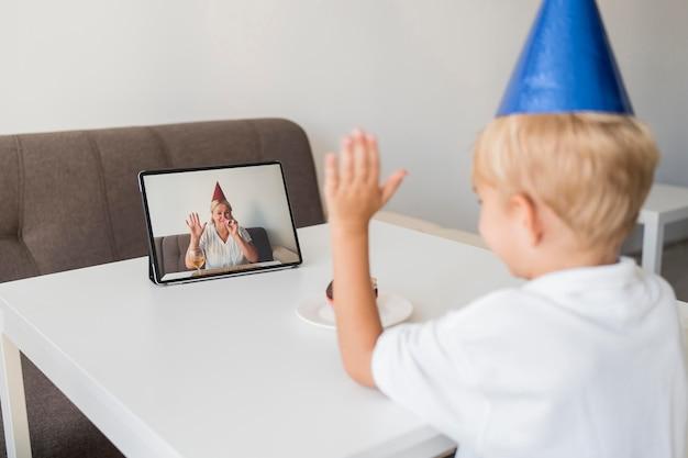 Criança em quarentena em casa comemorando aniversário com tablet