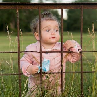 Criança em roupas cor de rosa atrás das grades do parque, segurando a máscara médica