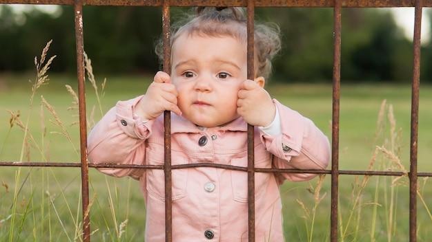 Criança em roupas cor de rosa atrás de barras de parque tiro médio