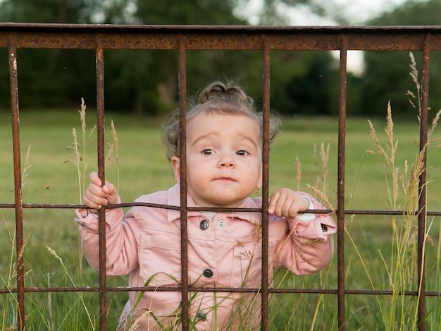 Criança em roupas cor de rosa atrás de barras de parque vista frontal