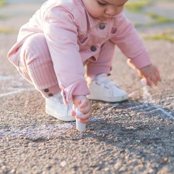 Criança em roupas cor de rosa, brincando com giz