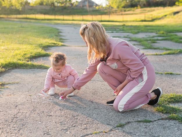 Criança em roupas cor de rosa e mãe desenho vista de longo