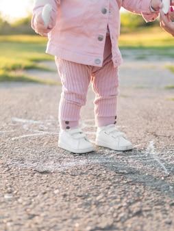 Criança em roupas cor de rosa em pé no chão sólido
