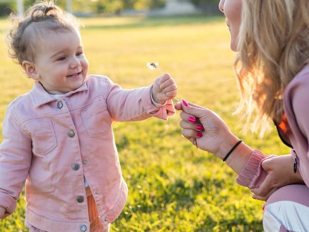 Criança em roupas cor de rosa, segurando uma flor