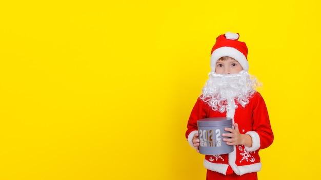 Criança em roupas de papai noel e com barba artificial que está segurando uma caixa com as palavras ano novo 2022