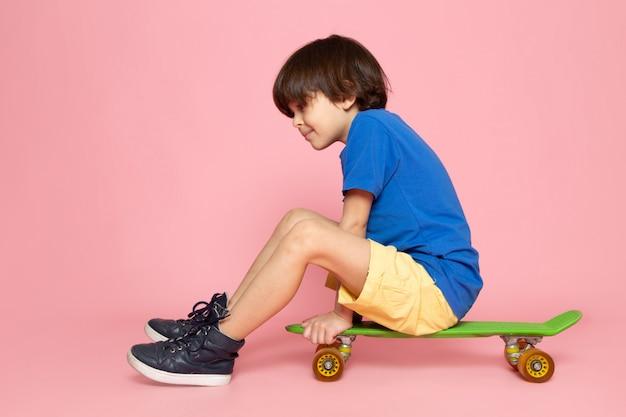 Criança em t-shirt azul andando de skate na parede rosa
