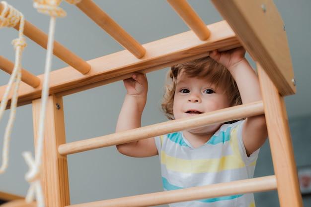 Criança em tenra idade está envolvida no complexo esportivo de madeira para crianças em casa.