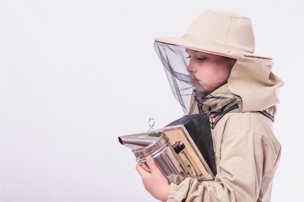 Criança em ternos de apicultor, posando em fundo branco do estúdio.