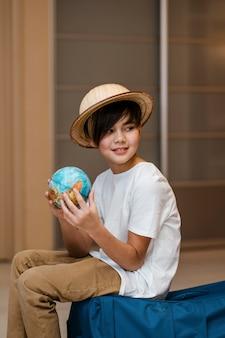 Criança em tiro médio posando na bagagem