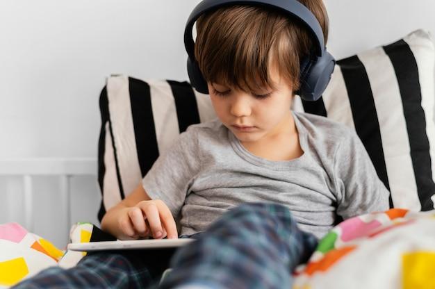 Criança em tiro médio usando fones de ouvido